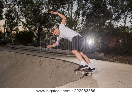 young American man practicing radical skate board having fun enjoying tricks jumps and stunts in concrete half pipe skating track in sport and healthy lifestyle concept