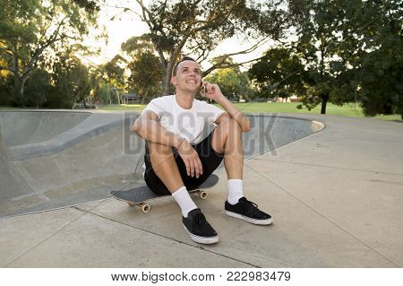 young happy and attractive American man 30s sitting on skate board after sport boarding training session talking on mobile phone in skateboarder conversation and communication