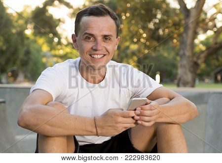 young happy and attractive American man 30s sitting on skate board after sport boarding training session using mobile phone sending internet social media text in skateboarder communication concept
