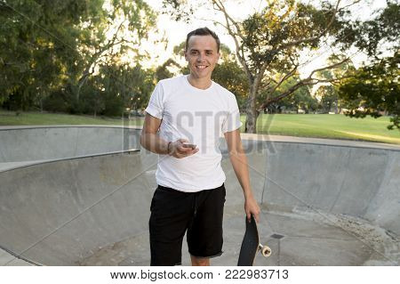 young happy and attractive American man 30s standing holding skate board after sport boarding training session using mobile phone at half pipe track park on Summer sunset