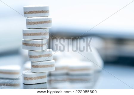 Macro shot of triangle shape tablet pills. Three layers tablet pills for indication antacid, digestive and gastric pain. Group of sandwich tablets pills on white background with copy space for text.