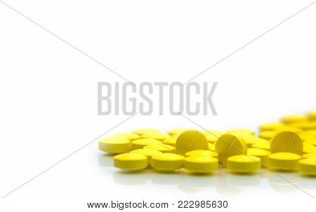 Yellow tablets pills isolated on white background with copy space. Pile of medicine. Painkiller tablets pills.