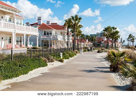 CORONADO, CALIFORNIA - JANUARY 20, 2018:  A sidewalk by beachfront cottages of the Hotel del Coronado, a historic beachfront hotel built in 1888, and formerly the largest resort hotel in the world.