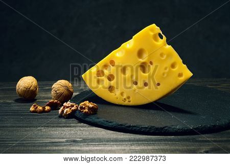 A piece of emmental cheese and walnuts on a dark wooden table.