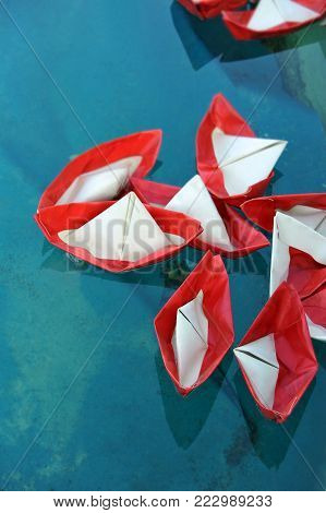 Red and white paper ship on water