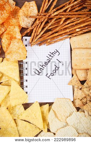 Inscription unhealthy food in notebook, crunchy potato crisps, breadsticks and cookies, concept of restriction eating unhealthy and salted food