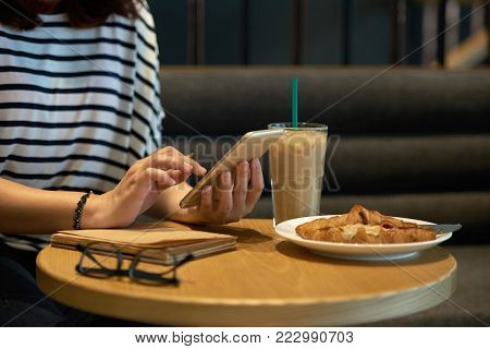 Hands of woman checking smarphone and eating breakfast