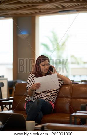 Business lady in casual clothes reading document and calling on the phone