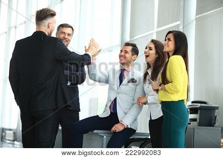 Business Team Achievement Success Mission Concept. Happy successful business team giving a high fives gesture as they laugh and cheer their success
