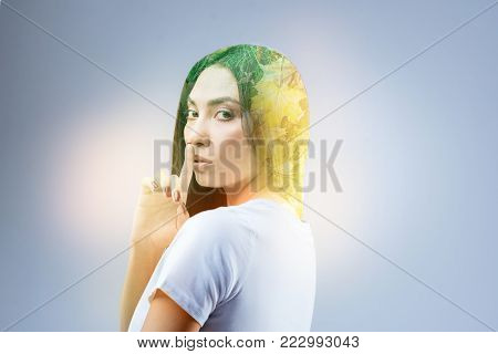 Delighted brunette turning head and raising forefinger while covering mouth