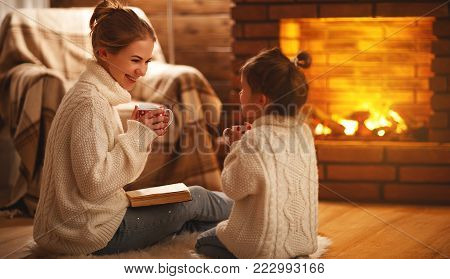 family mother and child daughter reading book on winter evening by fireplace