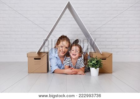 concept of housing, mortgage and relocation family mother and child  with roof and boxes near wall