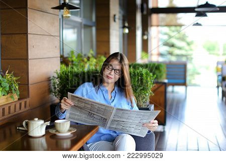 Young woman resting at restaurant with newspaper and cup of tea. Beautiful girl reading articles. Concept of Mass Media and spending free time at cafe.