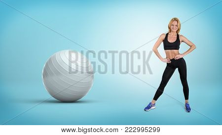 A young fit blonde woman stands with hands on her hips near a large silver exercise ball. Fitness training. Sports and health. Losing weight.