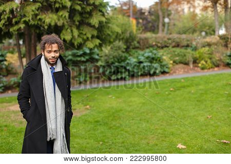 Young  guy strolling in autumn parkland and waiting photographer. Handsome boy dressed in black coat, grey scarf and blue tie, has long fleecy hair and cute smile. Concept of outside calm walking in ecological place.