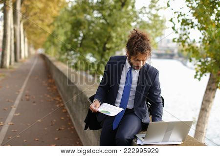 Young actor learning by heart new role for performance in Paris theatre with laptop near Eiffel Tower. Handsome man dressed in suit reading and gesticulating. Concept of preparing for speech on big scene.