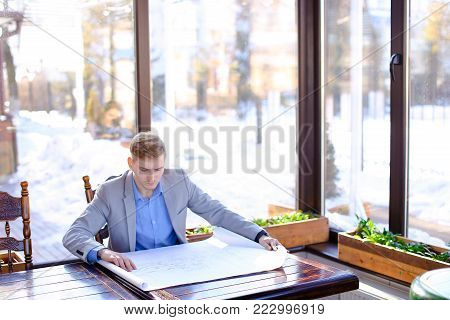 Student of architecture faculty sitting at cafe table and looking at drafting work. Young male person has blonde hair and wears grey suit. Concept of home task project and preparing before exam.