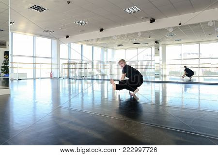 Male dance trainer sitting on twine and tilting trunk forward. Boy in good shape making stretching exercise at gym. Concept of dancing school spacious studio and physical training.