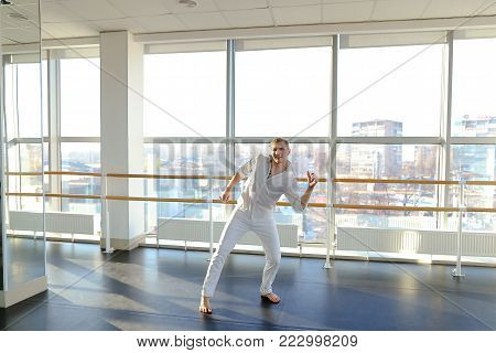 Male person making backwards somersault at gym studio . Young person wears black sport suit. Concept of acrobatic exercise.