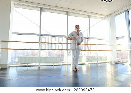 Graduate of dance school moves in white suit. Happy guy raving at gym. Concept of promotion to start dancing career.