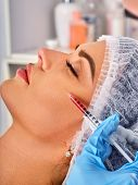 Filler injection for female face. Plastic aesthetic facial surgery and in clinic. Beauty woman giving injections in cosmetology room. Close up of female profile. poster