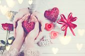 Valentine Gift. Young Couple Hands holding red heart gift over wooden background. St. Valentine's Day, Love concept. Top view, tabletop. Hands in Hands, romance, dating concept poster