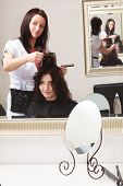 Brunette young beautiful woman in hairdressing beauty salon. Girl dying hair by hairstylist. Hairdresser colouring hair of female customer. In hairdressing studio. poster