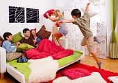 a young family is making a pillow-fight in their bedroom poster