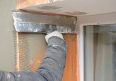 Contractor plastering wall  with putty knife, fiberglass mesh, plaster mesh after rigid insulation. House wall problem area insulation with stucco wall. poster