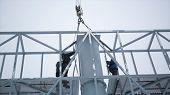 Builder on a Lift Platform at a construction site. Men at work. construction worker assembling scaffold on building site. Men assemble Billboard on tap. poster