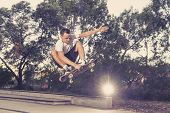 young American man practicing radical skate board jumping and enjoying tricks jumps and stunts in concrete half pipe skating track in sport and healthy lifestyle concept poster