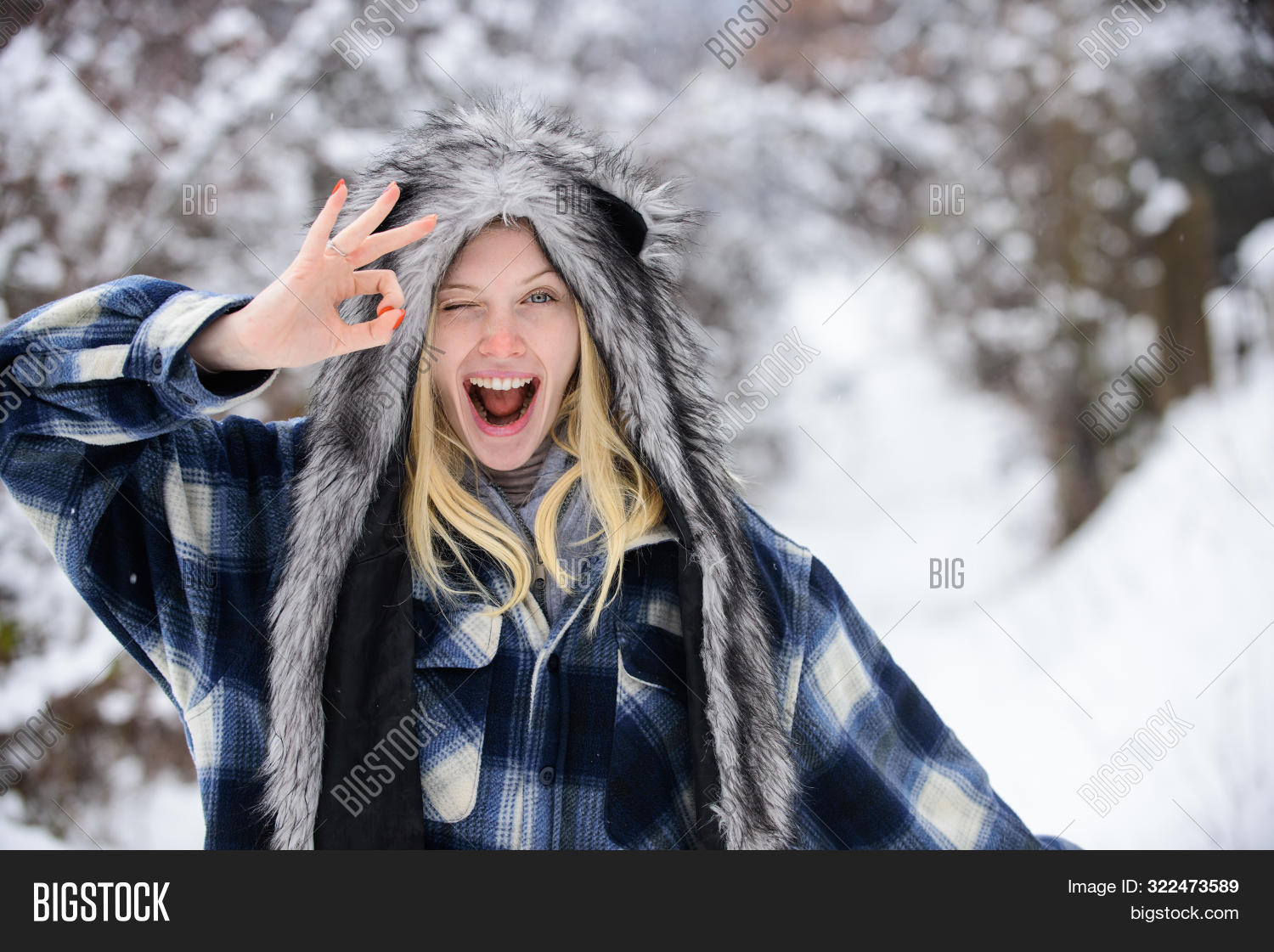 Winking Woman In Warm Coat, Hat Shows Sign Ok. Cold Winter Weather. Fashion Girl In Wintertime. Chri