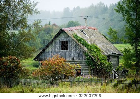 Old Abandoned Rickety Old Wooden House Without Windows With A Partially Missing Fence.