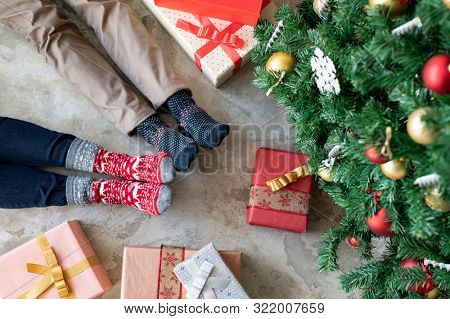 High angle view of loving couple feet near christmas tree with gifts. Top view of man and woman wearing knitted warm socks. Closeup legs of couple lying on floor and wearing xmas theme socks at home.