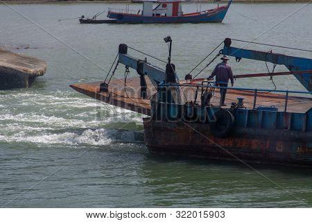 KOH PHANGAN, THAILAND - AUGUST 31, 2013: Blue ferry boat taking off in Koh Phangan island port.