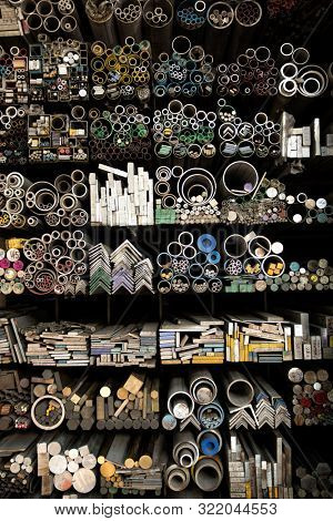 Close up various shape industrial steel products of metal profiles and tubes on warehouse shelf