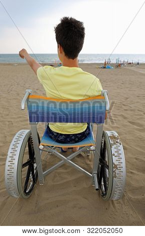 Disabled Boy On A Wheelchair On The Beach Points The Sea