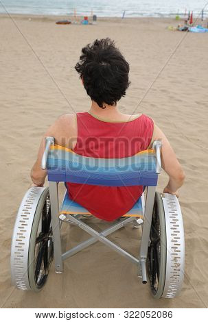 Young Man With Red Tshirt On The Wheelchair On The Beach In Summer