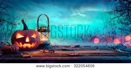 Halloween Pumpkin With Lantern On Table At Twilight