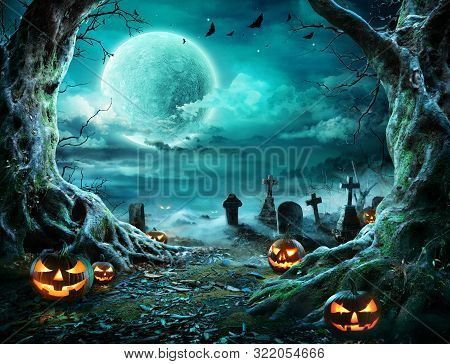 Jack O Lantern In Cemetery In Spooky Night With Full Moon - Halloween