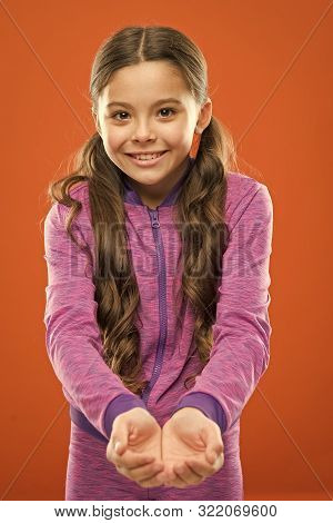 Look Here. Kid Happy Smiling Face Show Something In Both Hands Copy Space. Girl Demonstrate Product.