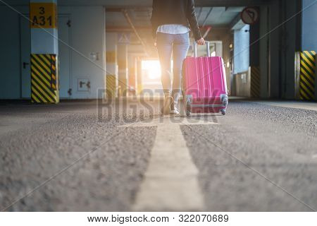 Image From Back Of Blonde With Pink Suitcase Walking Along Passage At Airport, Blurred Background. S