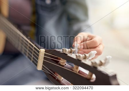 Blurred Guitar Player Twisting Pegs On Headstock While Tuning Instrument During Rehearsal