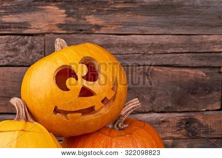 Funny Halloween Pumpkin On Wooden Background. Carved Haloween Pumpkin With Happy Face On Rustic Back