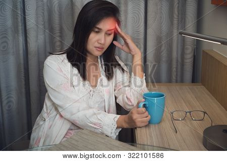 Asian Woman In White Satin Nightgown With Hard Headache Holding. Female Is Suffering From A Headache
