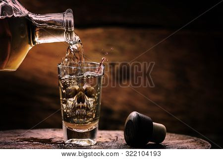 Drink Bottle And Glass With Alcohol Content. Image Of Translucent Skull In Glass. Alcoholism, Addict