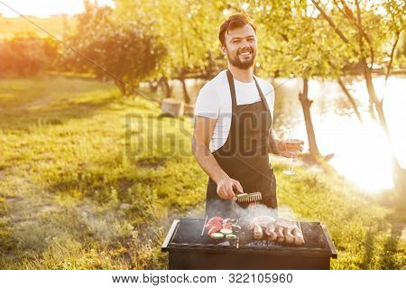 Smiling Man Frying Frankfurters And Vegetables On Grill On Lake Shore And Relishing Wine While Looki