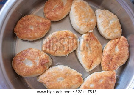 Fry Delicious Homemade Lush Pies With A Variety Of Fillings In Hot Vegetable Oil On. Pies Are Fried