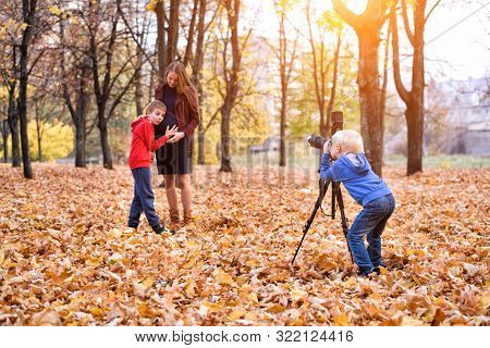 Little Blond Boy With A Big Slr Camera On A Tripod. Photographs A Pregnant Mother And Son. Family Ph