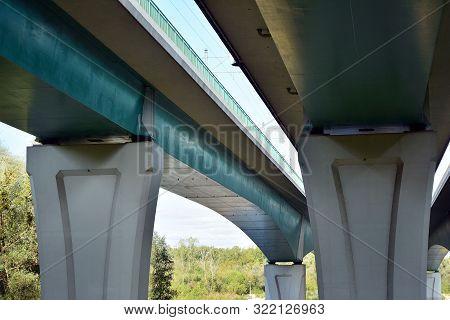Bottom View Of A Huge Flyover Motorway, Blue Sky, Large Pillars.